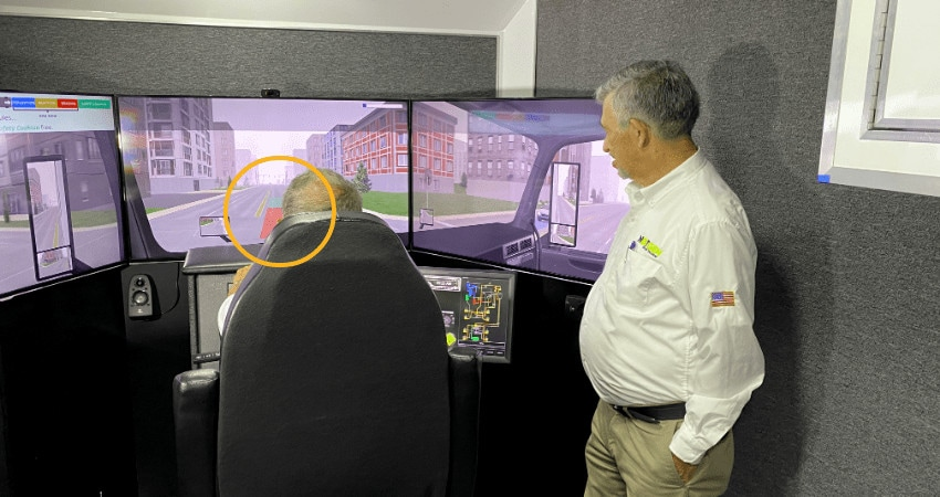 A Student And Trainer Going Through A Defensive Driver Training Session That Incorporates Risk Zones In The Simulator