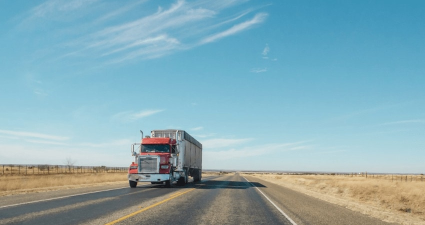 A Red And White Truck Driving Down A Highway With Clear Blue Skies And Sand On Either Side Of The Highway
