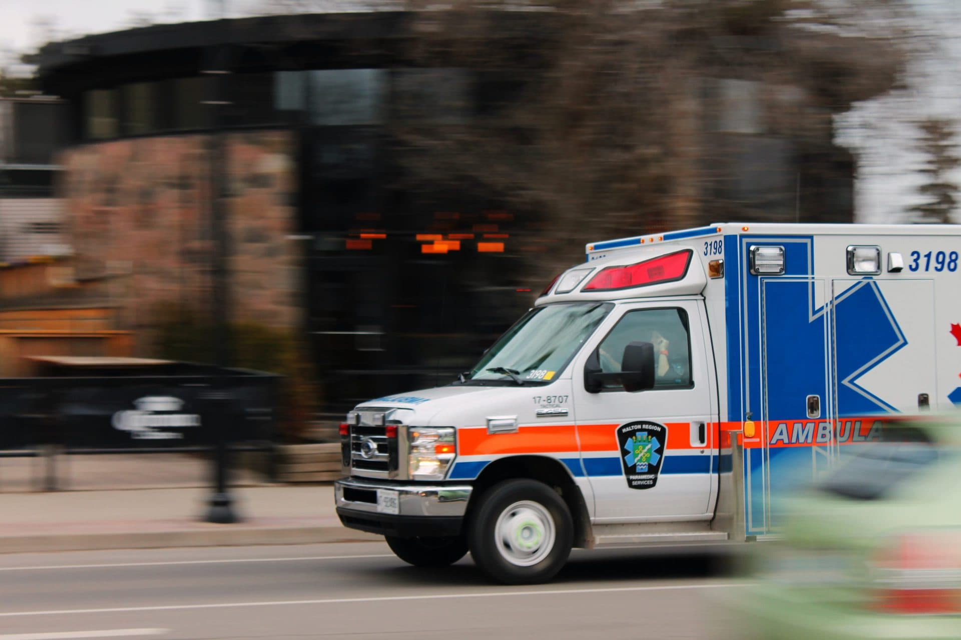 Ambulance Truck Driving Down A Street